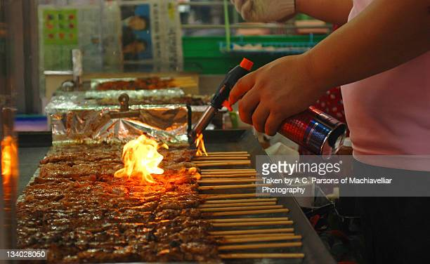 Man using torch to barbeque meat