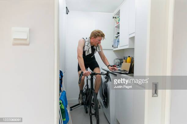 man using turbo trainer in utility room - exercising stock pictures, royalty-free photos & images