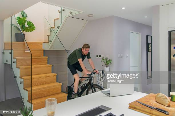 man using turbo trainer indoors - shorts stock pictures, royalty-free photos & images