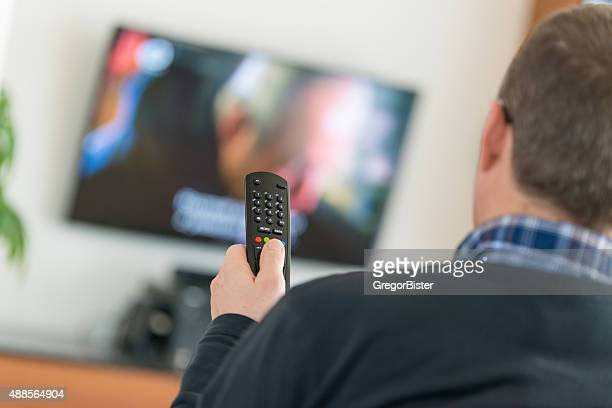 Man using TV Remote Control