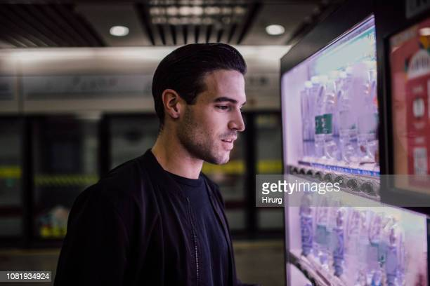 man using vending machine - vending machine stock photos and pictures