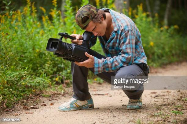 Man using video camera while crouching on dirt road