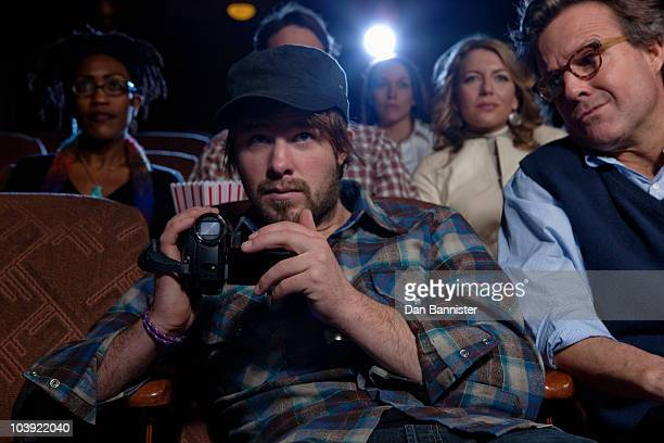 man using video recorder in movie theatre - copyright stock photos and pictures
