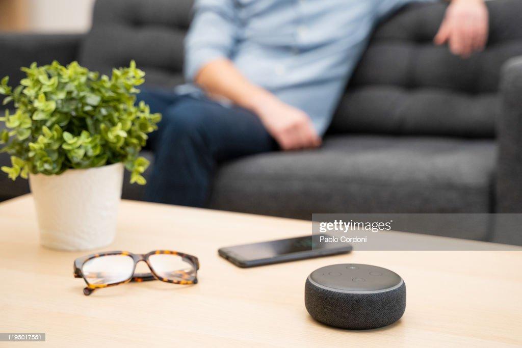 Mann mit virtuellem Assistenten und smartem Lautsprecher zu Hause : Stock-Foto