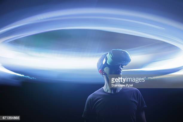 Man using Virtual Reality goggles, light around