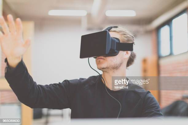 man using virtual reality headset in a working environment - vanguardians stock pictures, royalty-free photos & images