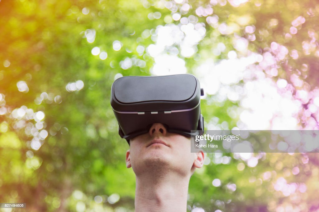 Man using virtual reality headset in visionary forest : Stock Photo