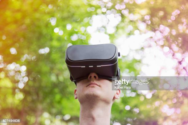 Man using virtual reality headset in visionary forest