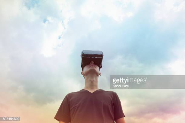 Man using virtual reality headset under the visionary sky