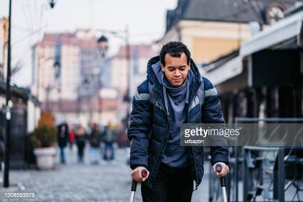 ダウンタウンの怪我を歩くために歩く杖を使用している男 - 杖 ストックフォトと画像