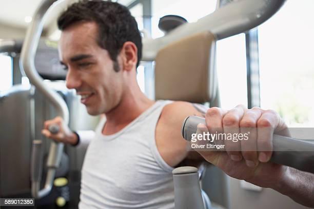 man using weight machine - oliver eltinger stock-fotos und bilder