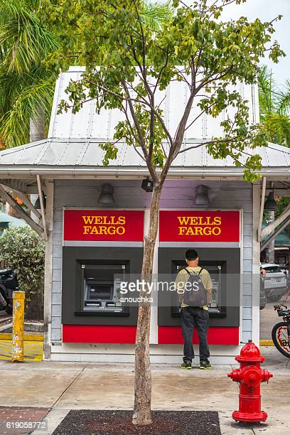 man using wells fargo atm on duval street, key west - duval street stock pictures, royalty-free photos & images