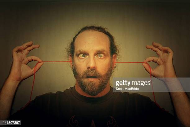 man using wool to floss his mind through his ears - scott macbride stock pictures, royalty-free photos & images