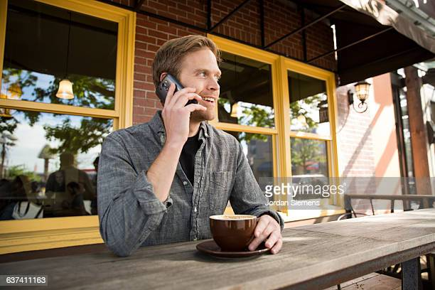 A man usinga cell phone at a coffee shop.