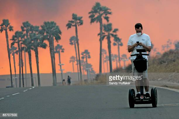 Man usues his cell phone while riding a Segway November 15, 2008 as the glow from a fire is seen in the distance in Yorba Linda, California. Strong...