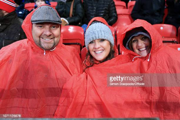 Man Utd fans use a red poncho to shelter from the rain during the Premier League match between Manchester United and Fulham at Old Trafford on...