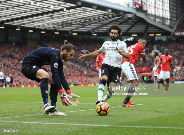 Man Utd goalkeeper David De Gea gathers the ball before Mohamed Salah of Liverpool can reach it during the Premier League match between Manchester...