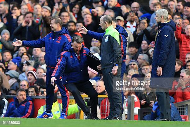 Man Utd manager Louis van Gaal falls to the ground as he imitates a dive in front of fourth official Mike Dean during the Barclays Premier League...