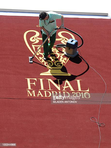 A man vacums the carpet at the entrance to the pitch before the UEFA Champions League final football match Inter Milan against Bayern Munich at the...