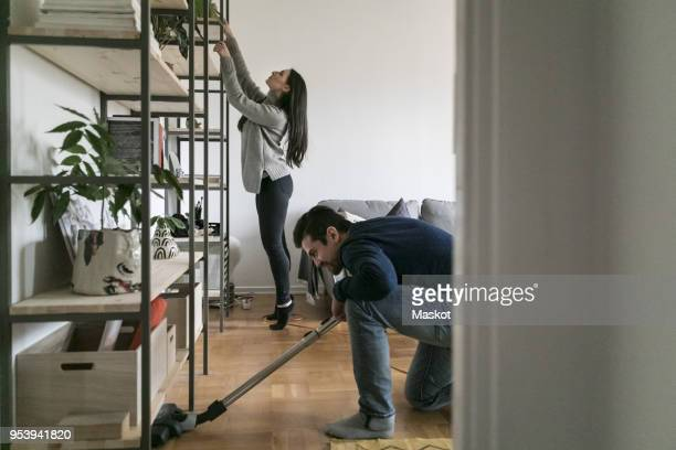 Man vacuuming floor while woman cleaning shelf at home
