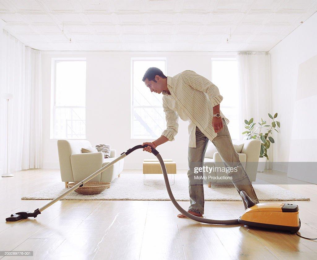 Man vacuuming living room floor, side view : Foto de stock
