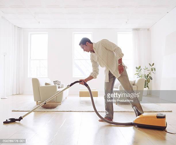 Man vacuuming living room floor, side view