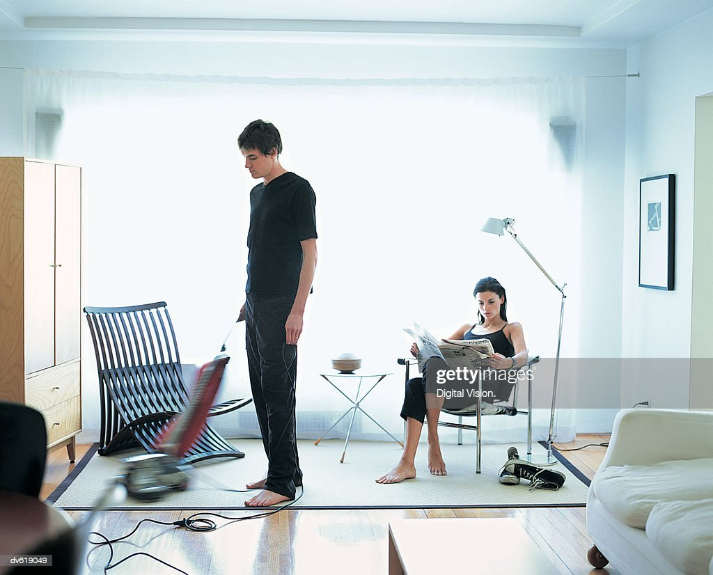 Man Vacuuming, While Woman Reads Newspaper : Stock Photo