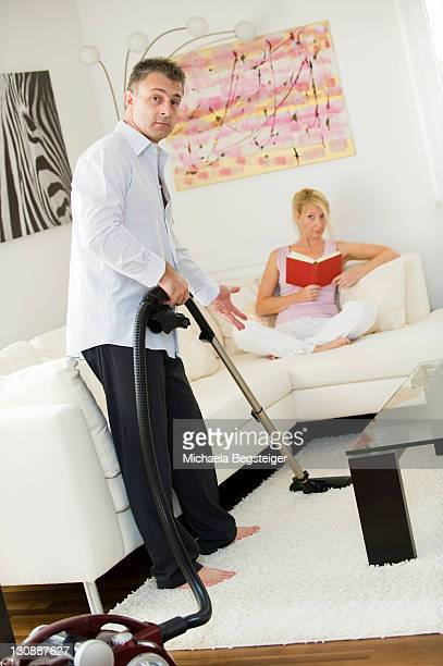 Man vacuuming, woman sitting on a sofa reading a book