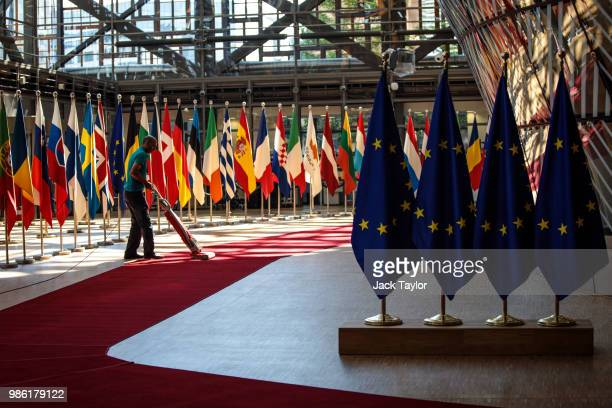 A man vacuums a red carpet at the Council of the European Union on the first day of the European Council leaders' summit on June 28 2018 in Brussels...