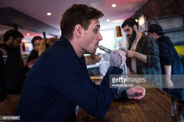 A man vapes or smokes an electronic cigarette at Henley Vaporium on April 29 2014 in New York City A new law that goes into effect today in New York...