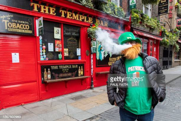 A man vapes outside a closed pub in the popular Temple bar area of Dublin on March 17 as St Patrick's Day festivities are cancelled and pubs shut in...