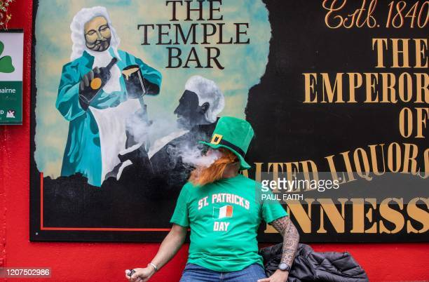 TOPSHOT A man vapes outside a closed pub in the popular Temple bar area of Dublin on March 17 as St Patrick's Day festivities are cancelled and pubs...