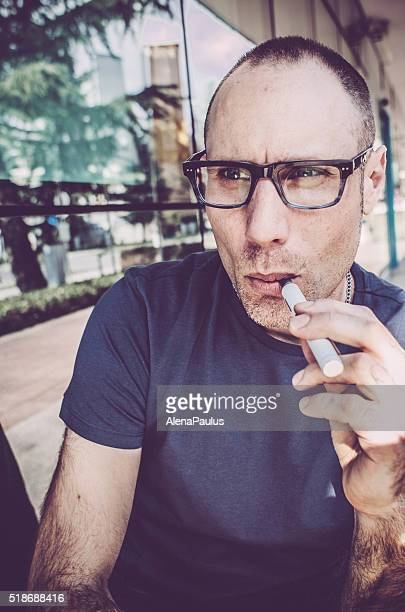 Man vaping outdoors, people using electronic cigarettes in daily life