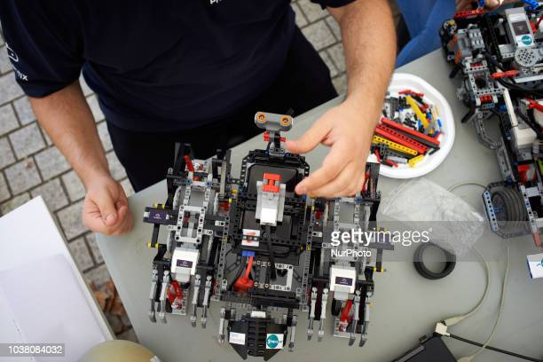 A man verifies his walking robot made in Lego A robots race took place in Toulouse Machines are either cars or walking robots They were supposed to...