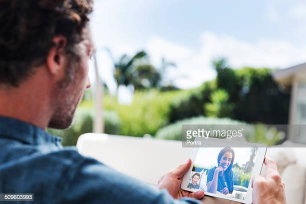 Man video conferencing with woman at yard