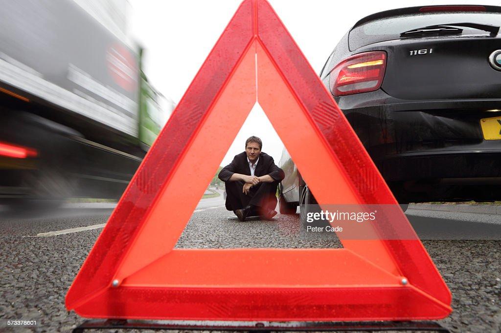 Man viewed through warning triangle, broken car : Stock Photo