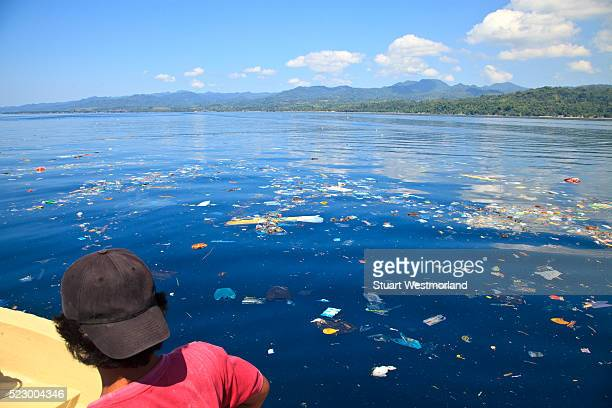 man viewing garbage floating on surface of the water near ambon - flotter sur l'eau photos et images de collection