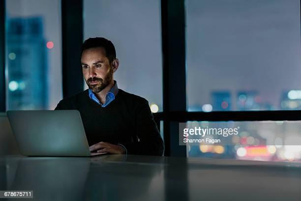 man viewing laptop computer in office at night - businessman - fotografias e filmes do acervo
