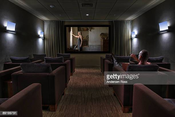 man viewing movie in home theater - film moving image stock pictures, royalty-free photos & images