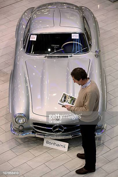 A man views a 1955 MercedesBenz 300SL Gullwing Coupe displayed in MercedesBenz World prior to its auction on December 6 2010 in Weybridge England The...