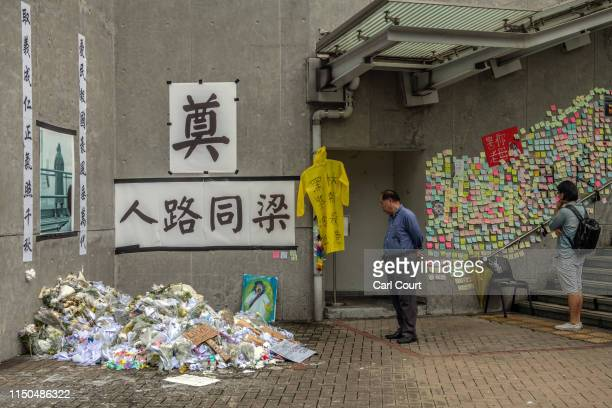 A man views a flowers and tributes to a man who died from a fall during a protest as another reads postit note messages near the Legislative Council...