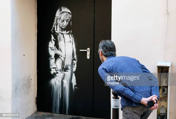 A man views a recent artwork attributed to street artist Banksy on June 26 2018 in Paris France Yesterday a new artwork attributed to street artist...