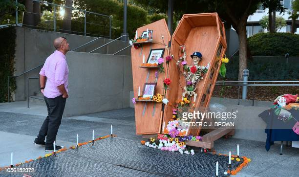 TOPSHOT A man views a skeleton wearing a Dodgers cap in a coffin at a Day of the Dead display dedicated to a variety of causes in downtown Los...