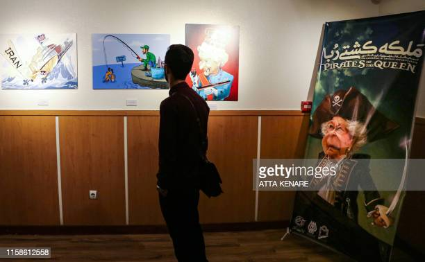 A man views caricatures at the Pirates of the Queen cartoon exhibition showing artwork by Iranian artists portraying Britain's Queen Elizabeth II as...