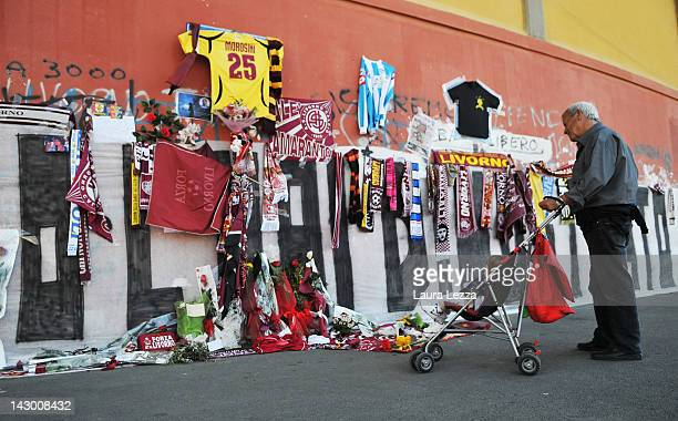 Man views floral and graffiti tributes outside Armando Picchi Stadium, where the coffin of footballer Piermario Morosini was displayed for fans and...