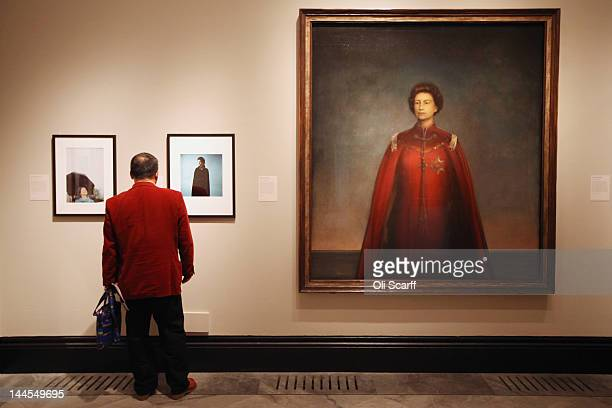 A man views images of Her Majesty Queen Elizabeth II inculding one by artist Pietro Annigoni entitled 'Queen Elizabeth II' in the National Portrait...
