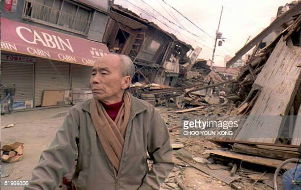 A man views the destruction from the 17 January earthquake on a central Kobe Japan street 19 January At least 3500 people have already been confirmed...