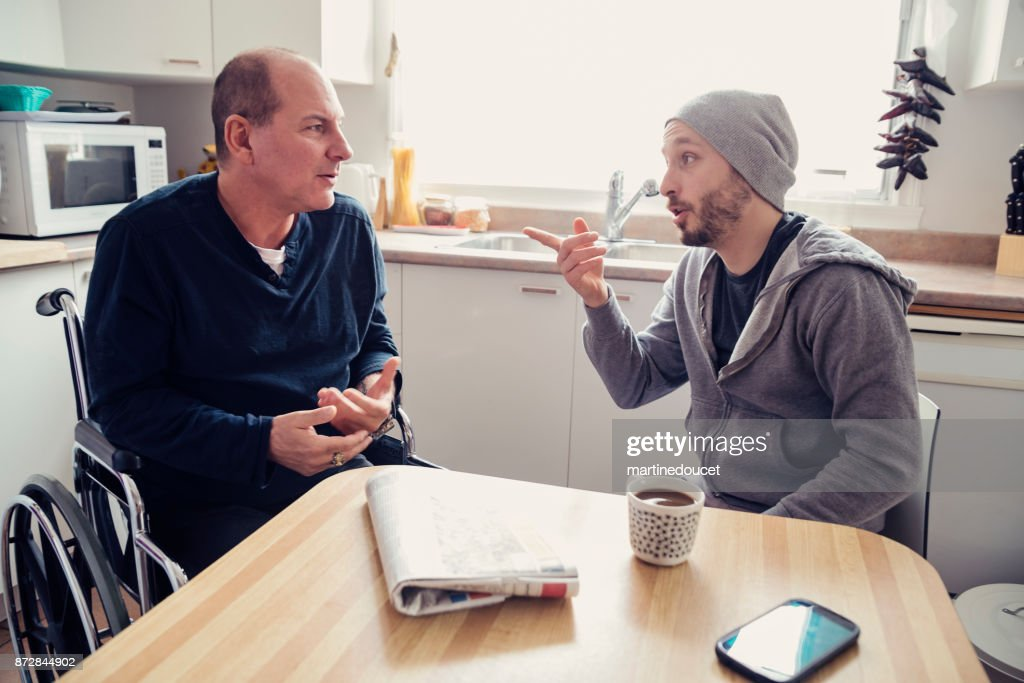 Man visiting a temporary disabled friend and having a coffee. : Stock Photo