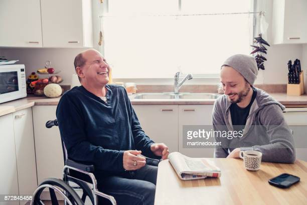 man visiting a temporary disabled friend and having a coffee. - adult stock pictures, royalty-free photos & images