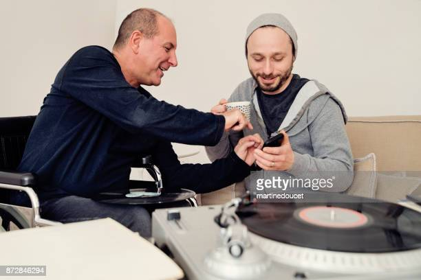 man visiting a temporary disabled friend enjoying vintage records. - disability collection stock pictures, royalty-free photos & images